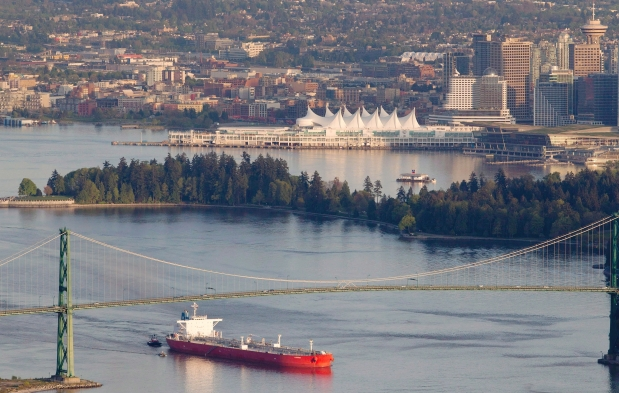 An oil tanker is guided by tug boats as it goes under the Lions Gate Bridge at the mouth of Vancouver Harbour. Photograph by: Jonathan Hayward, The Canadian Press
